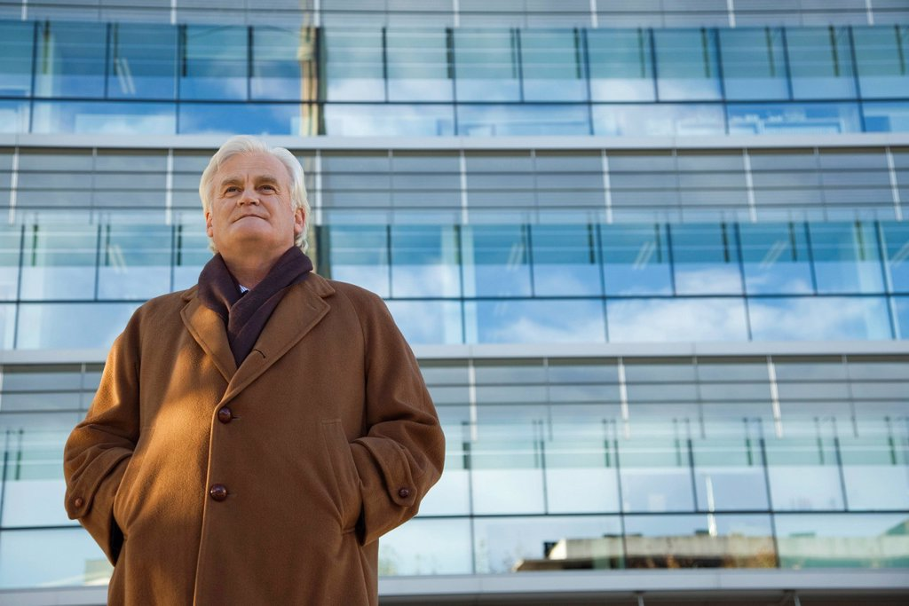 Mature man standing in front of building, looking away, portrait : Stock Photo