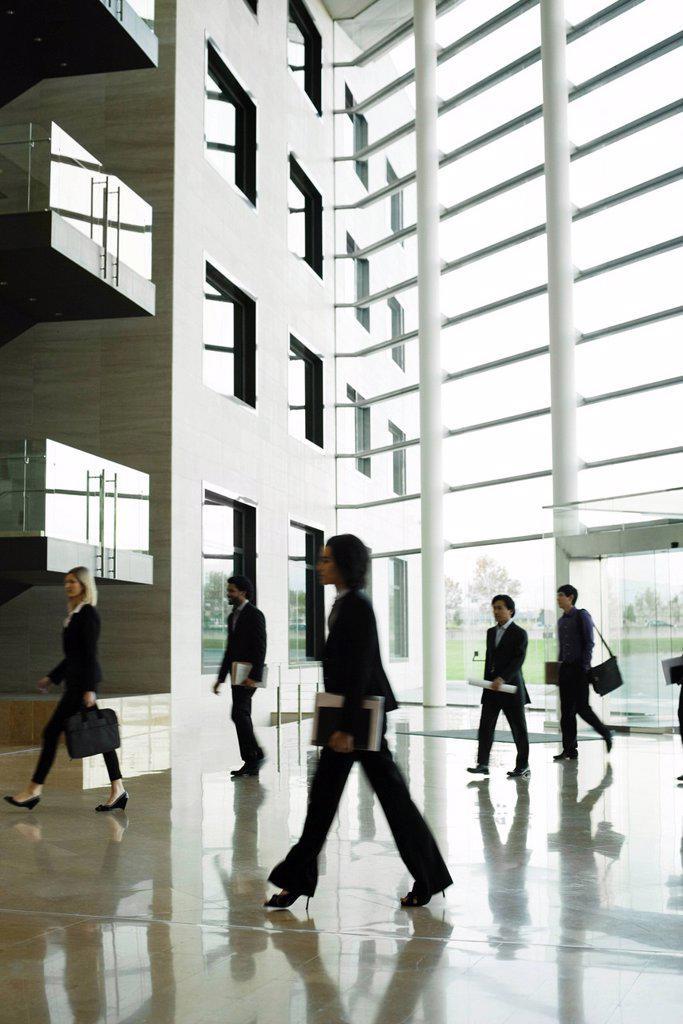 Executives walking in lobby : Stock Photo