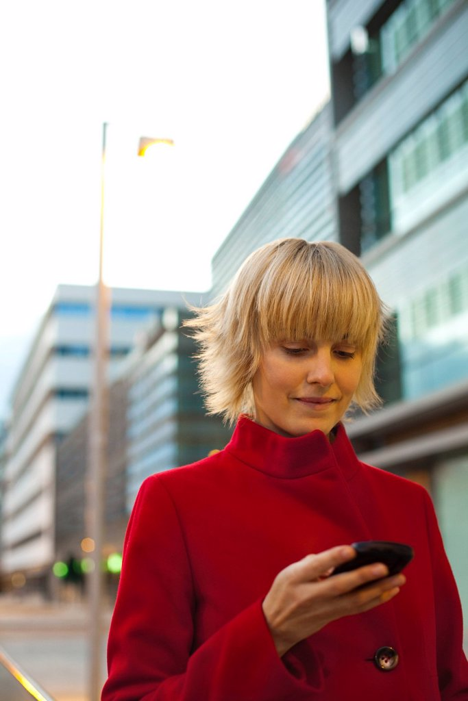 Young woman using cell phone, portrait : Stock Photo