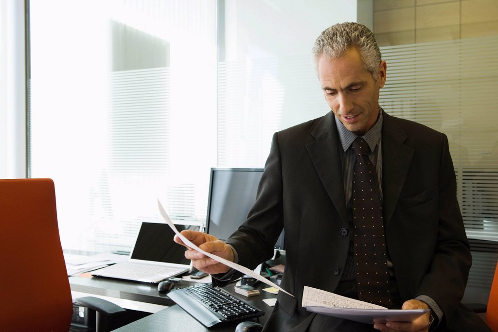 Stock Photo: 1569R-9068973 Executive reading report in office