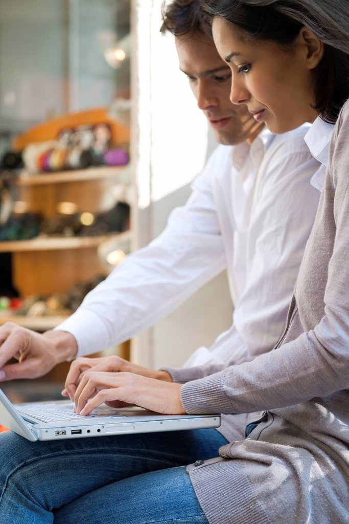 Couple using laptop computer together in cafe : Stock Photo