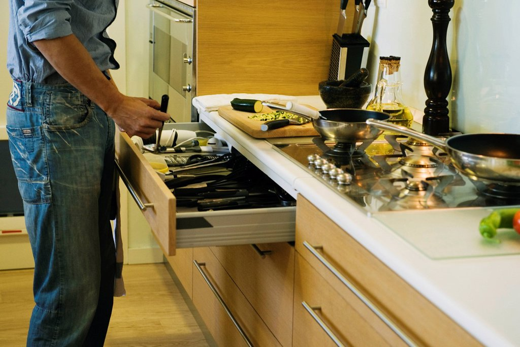 Man cooking, taking utensil out of drawer : Stock Photo