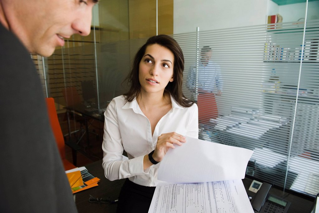 Executive reviewing document with colleague : Stock Photo