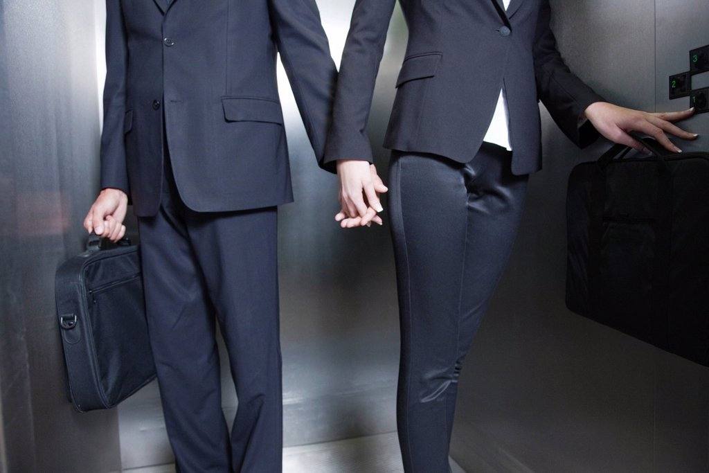 Stock Photo: 1569R-9069379 Professionals holding hands in elevator, cropped