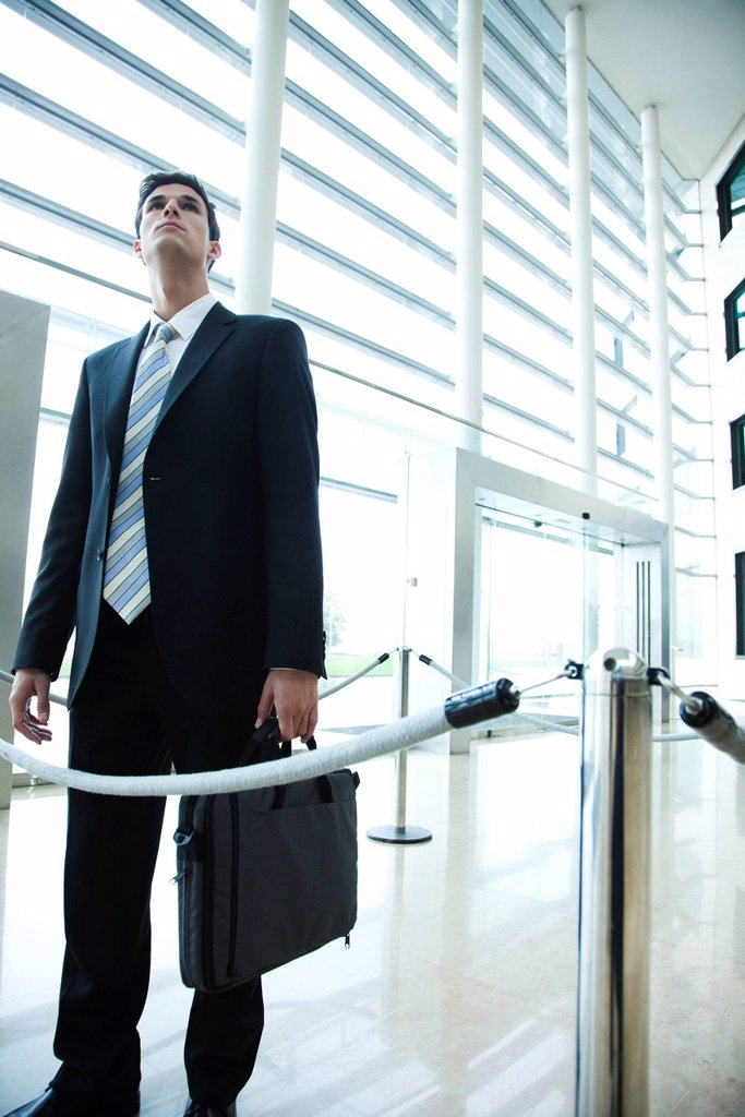 Businessman standing in lobby, looking up : Stock Photo