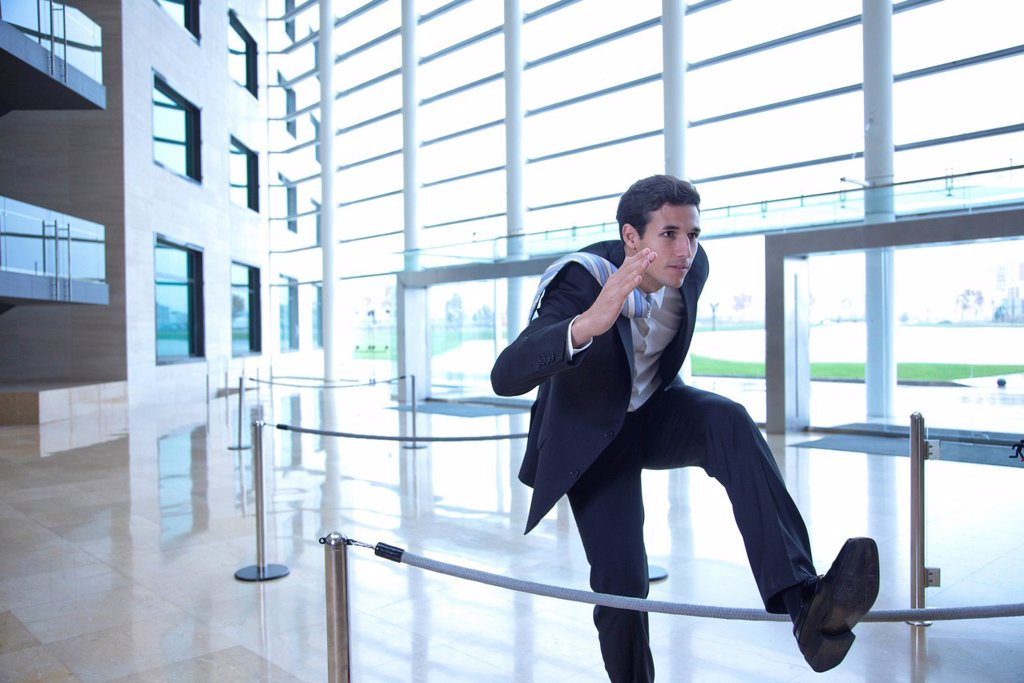 Businessman jumping over rope in lobby : Stock Photo