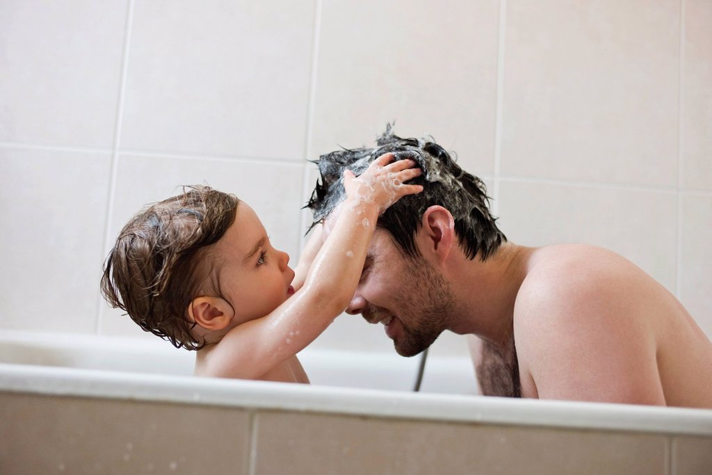 Toddler boy washing father´s hair in bath : Stock Photo
