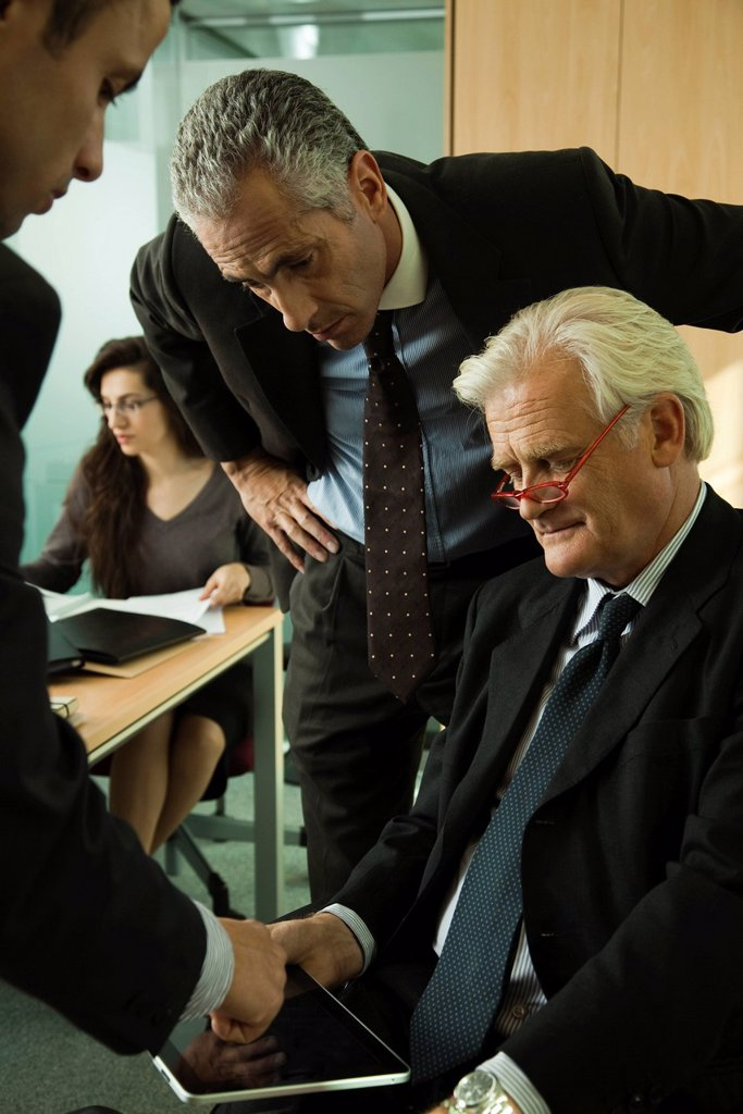 Stock Photo: 1569R-9069759 Young businessman explaining to mature executives how to use digital tablet