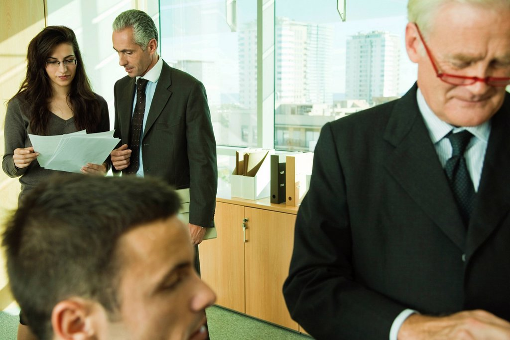 Executives working with young associates in office : Stock Photo
