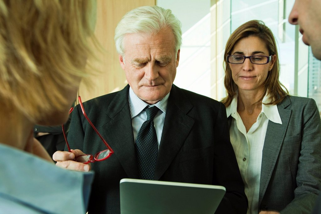 Executives examining information on digital tablet : Stock Photo