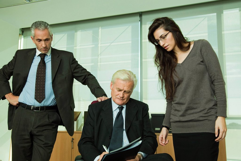 Executive signing paperwork, colleagues standing by his side : Stock Photo
