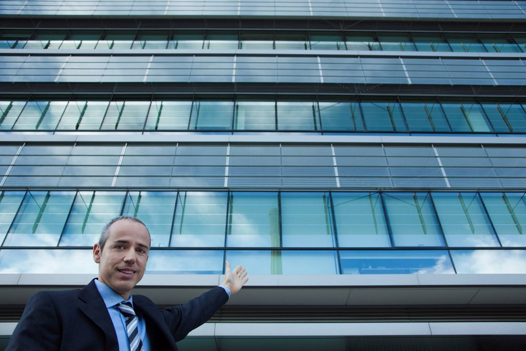 Executive gesturing at office building and smiling : Stock Photo