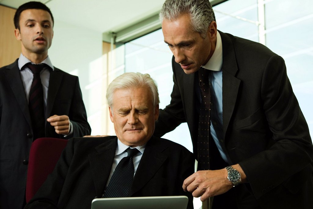 Stock Photo: 1569R-9069813 Executives looking down at digital tablet
