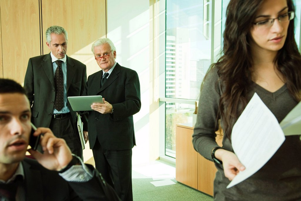 Stock Photo: 1569R-9069816 Executives using digital tablet, young associates working in foreground