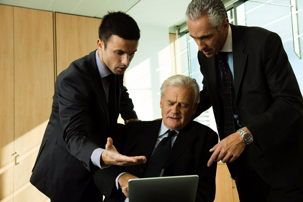 Executives in discussion while looking down at digital tablet : Stock Photo