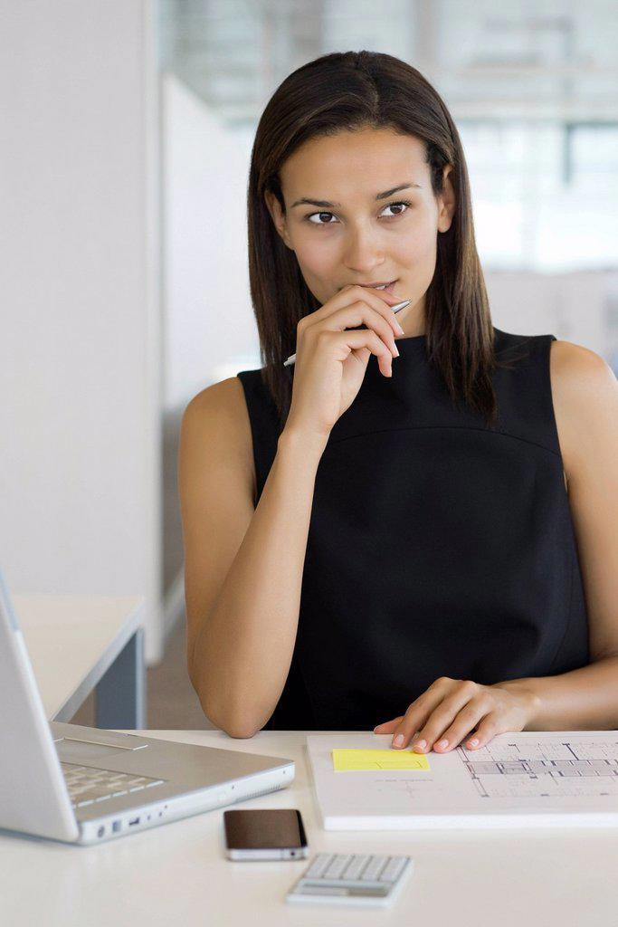 Stock Photo: 1569R-9070047 Businesswoman contemplating blueprint, portrait