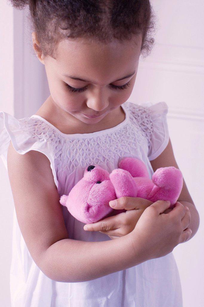 Little girl holding teddy bear affectionately : Stock Photo