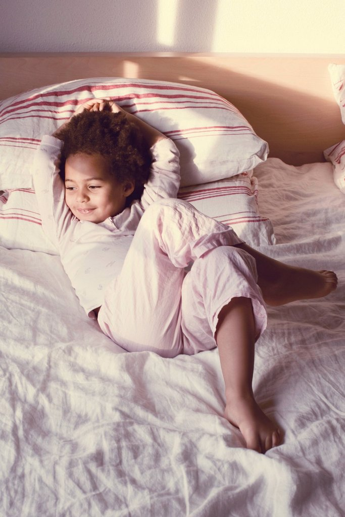 Stock Photo: 1569R-9070072 Little girl lying on bed in pajamas