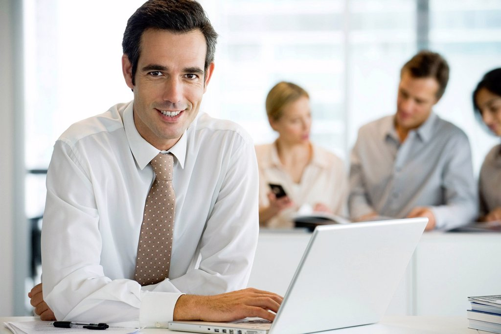 Stock Photo: 1569R-9070185 Smiling businessman using laptop computer