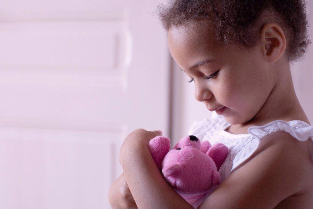 Stock Photo: 1569R-9070204 Little girl holding teddy bear affectionately