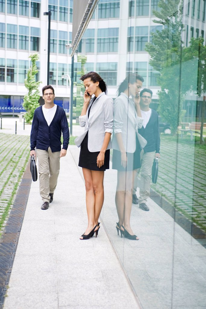 Woman talking on cell phone outside of office building, man walking by : Stock Photo
