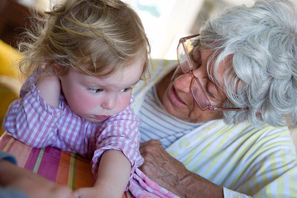 Stock Photo: 1569R-9070249 Grandmother comforting toddler granddaughter