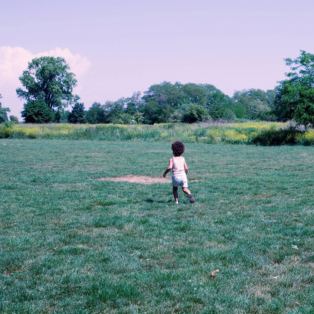 Little girl walking on meadow : Stock Photo