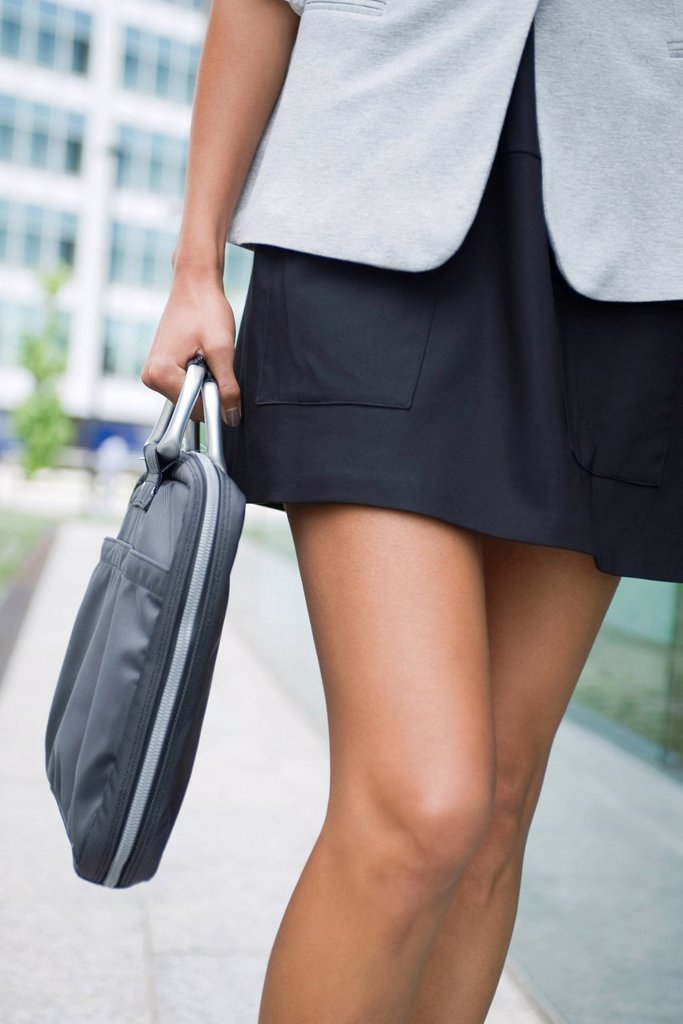 Stock Photo: 1569R-9070362 Woman carrying briefcase, mid section
