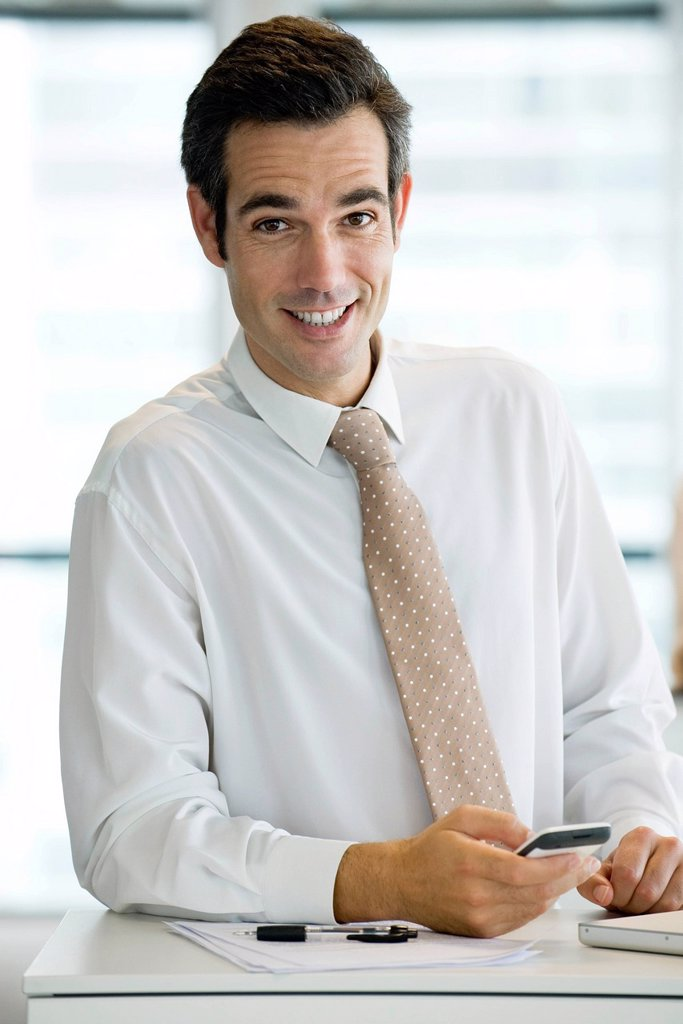 Businessman holding cell phone, portrait : Stock Photo