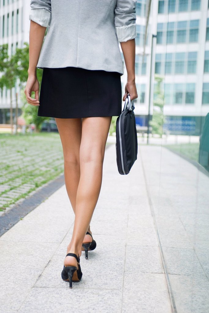 Woman walking with briefcase, low section : Stock Photo