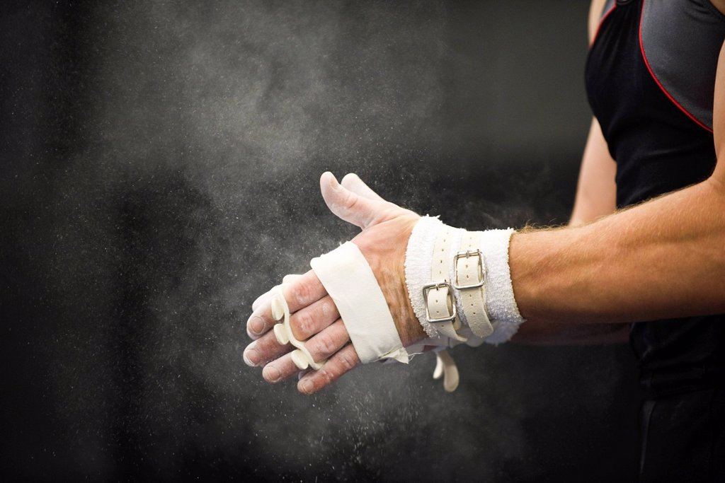 Stock Photo: 1569R-9070510 Gymnast applying chalk power to hands in preparation