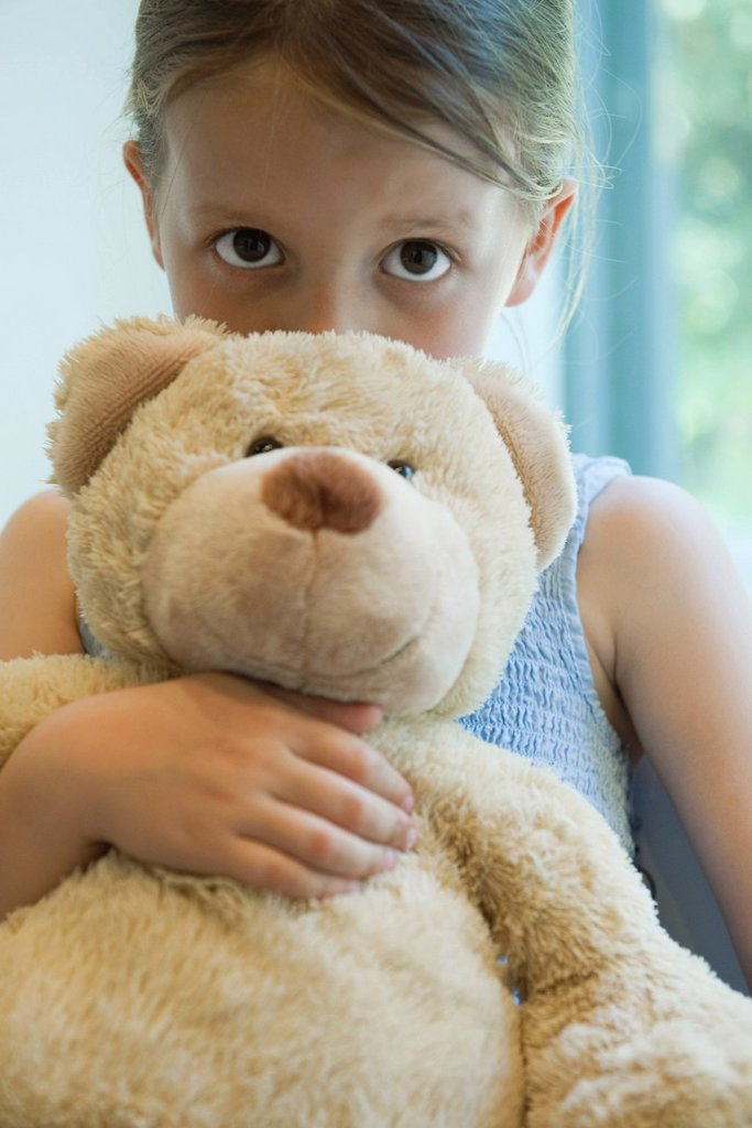 Little girl hugging teddy bear : Stock Photo