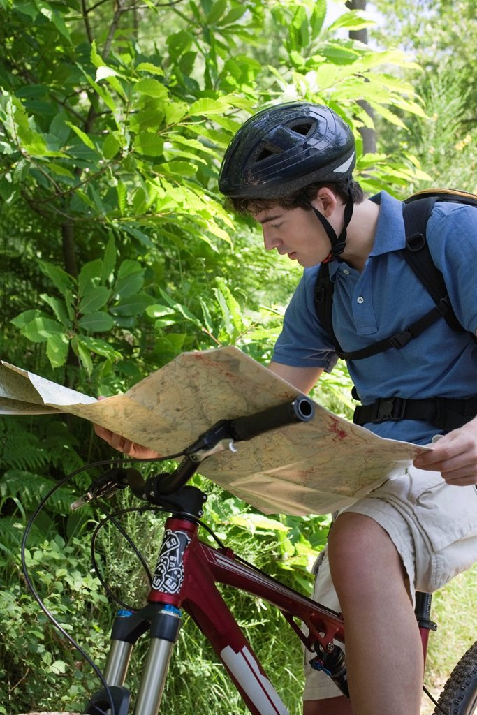 Man reading map on bicycle : Stock Photo