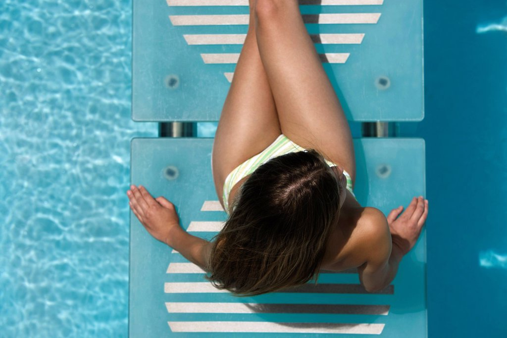 Woman relaxing on swimming pool footbridge : Stock Photo