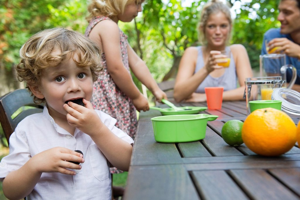 Boy enjoying outdoor snack with his family : Stock Photo