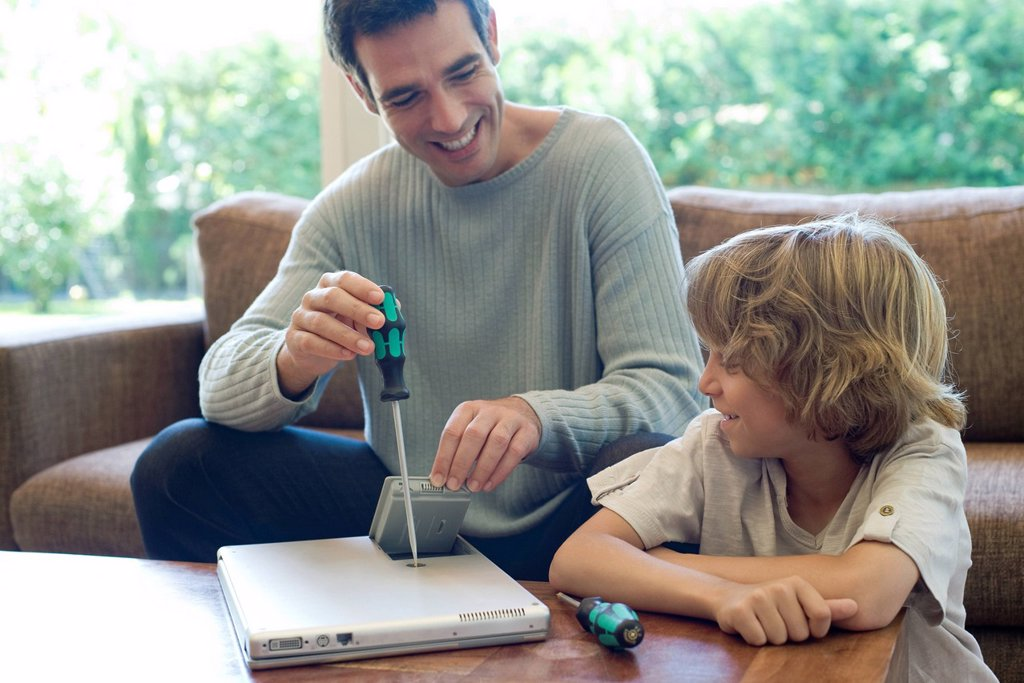 Son watching father repairing laptop computer : Stock Photo