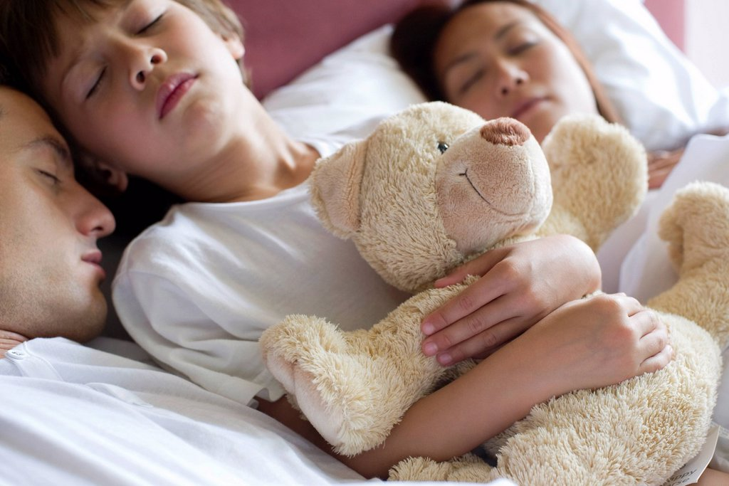 Stock Photo: 1569R-9071349 Boy sleeping in bed with his parents, holding teddy bear