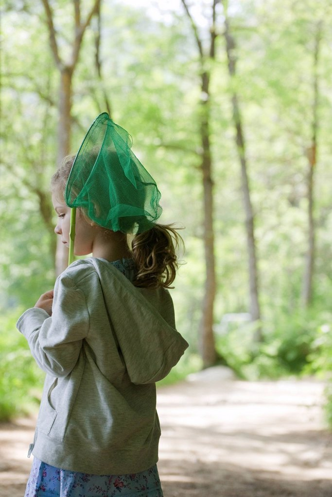 Stock Photo: 1569R-9071426 Girl carrying butterfly net in woods