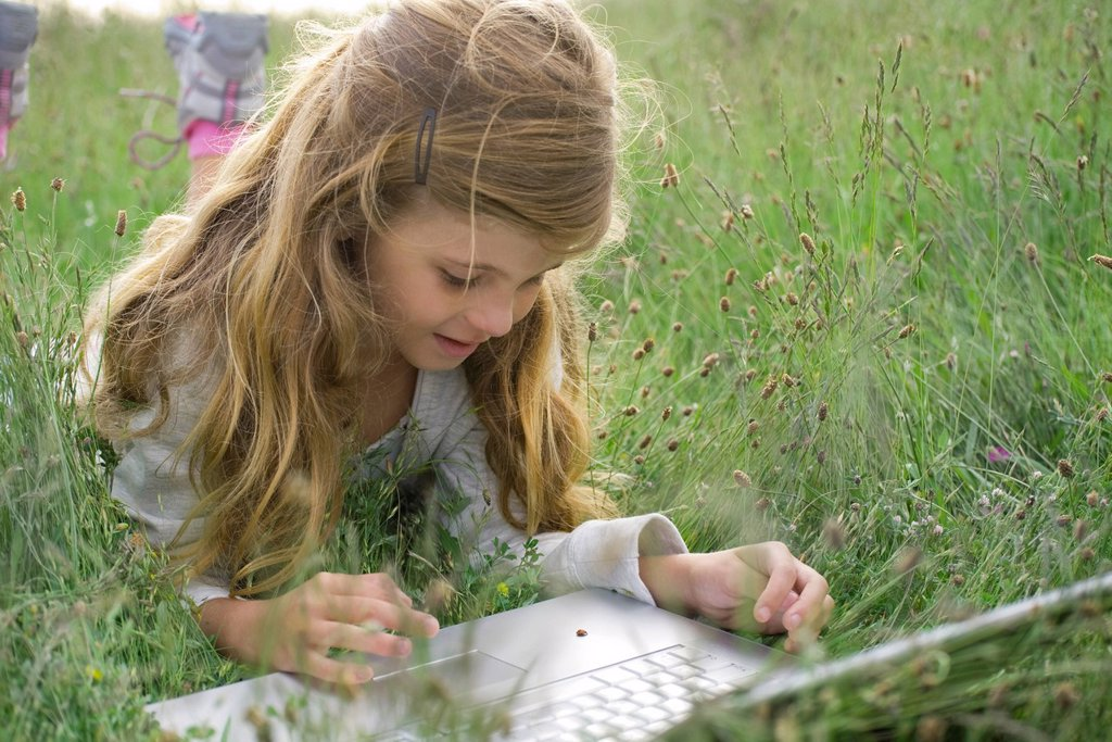 Stock Photo: 1569R-9071773 Girl lying in grass, watching ladybug crawling on laptop computer