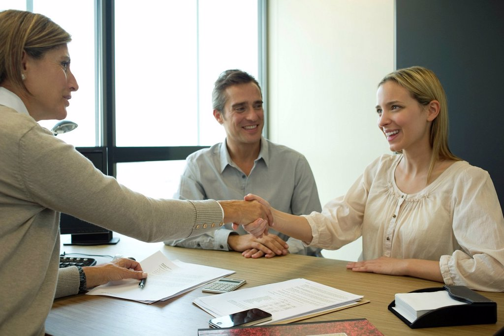 Businesswoman shaking hands with client in office : Stock Photo
