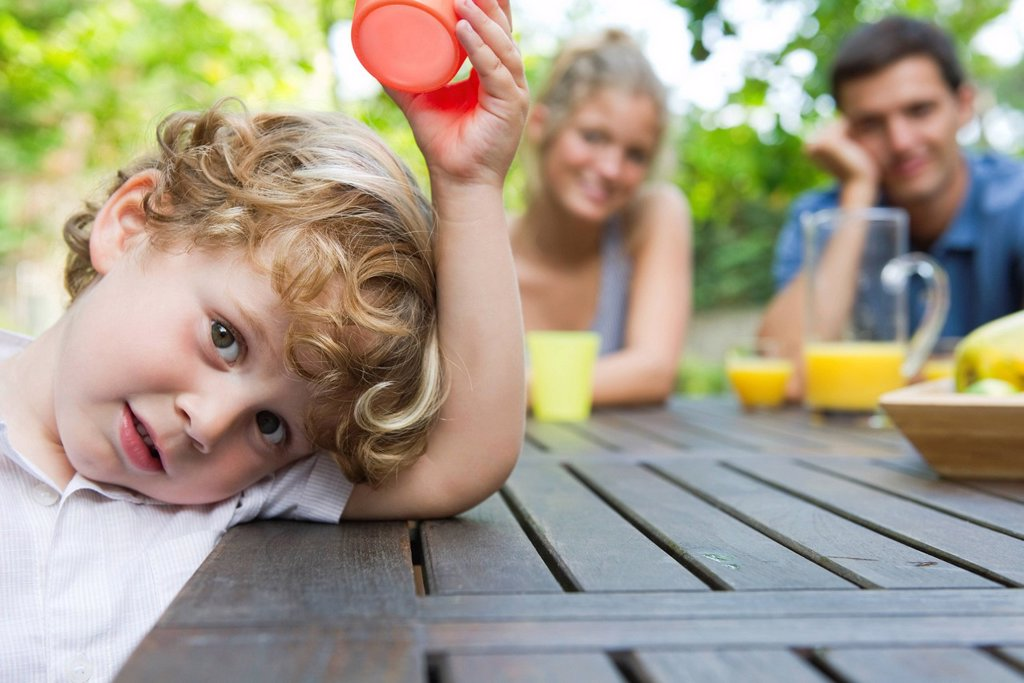 Little boy relaxing at picnic table with parents : Stock Photo