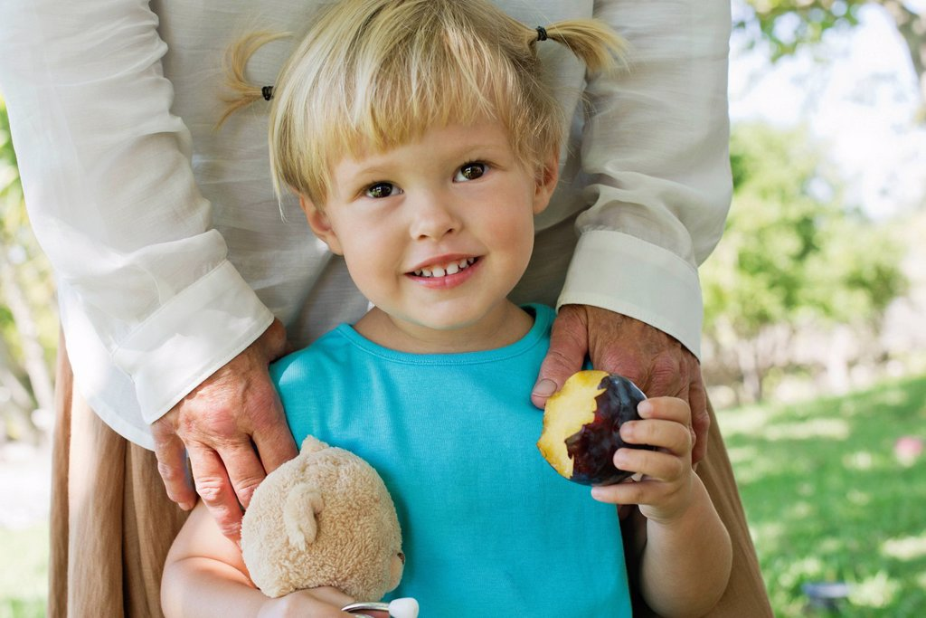 Little girl holding biten plum : Stock Photo