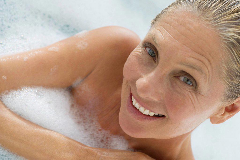 Stock Photo: 1569R-9072009 Mature woman enjoying bubble bath, tilt
