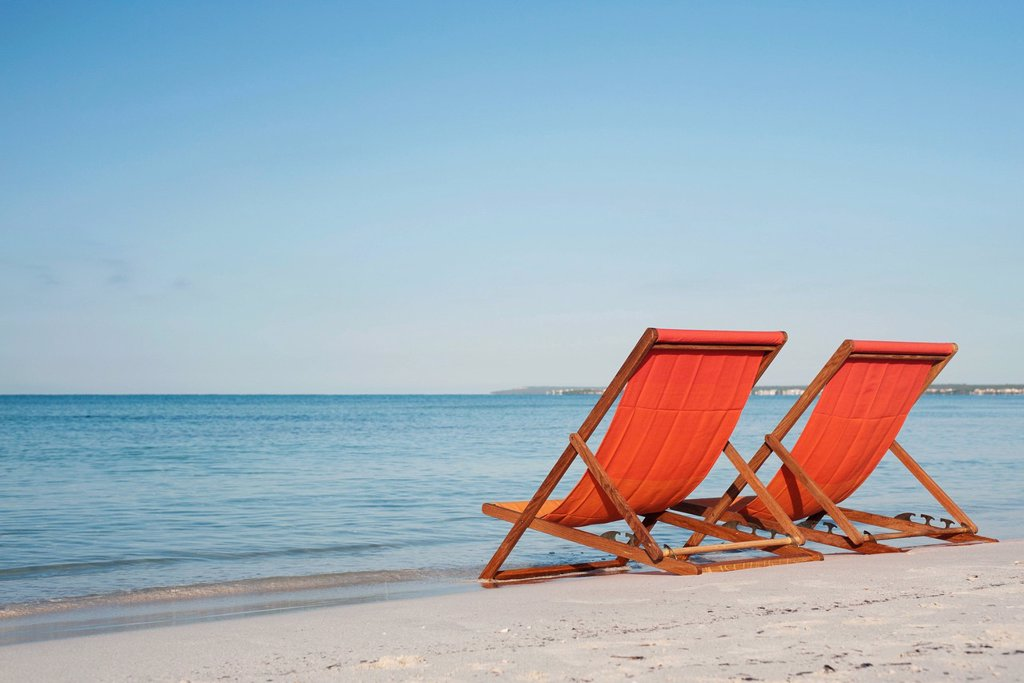 Stock Photo: 1569R-9072026 Empty deckchairs on beach