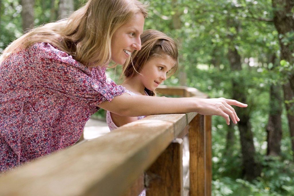 Mother and young daughter looking over railing together : Stock Photo