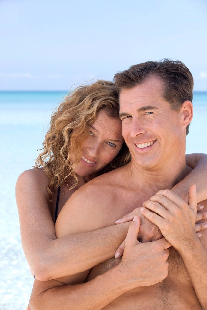 Stock Photo: 1569R-9072069 Couple embracing at beach, portrait