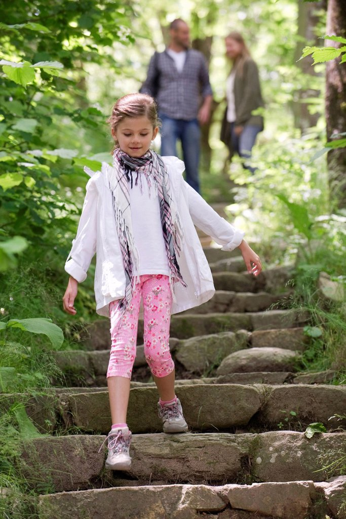 Stock Photo: 1569R-9072100 Girl walking down stone steps in woods, parents in background
