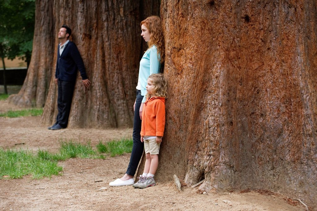 Mother and daughter leaning against tree, father standing separate in background : Stock Photo