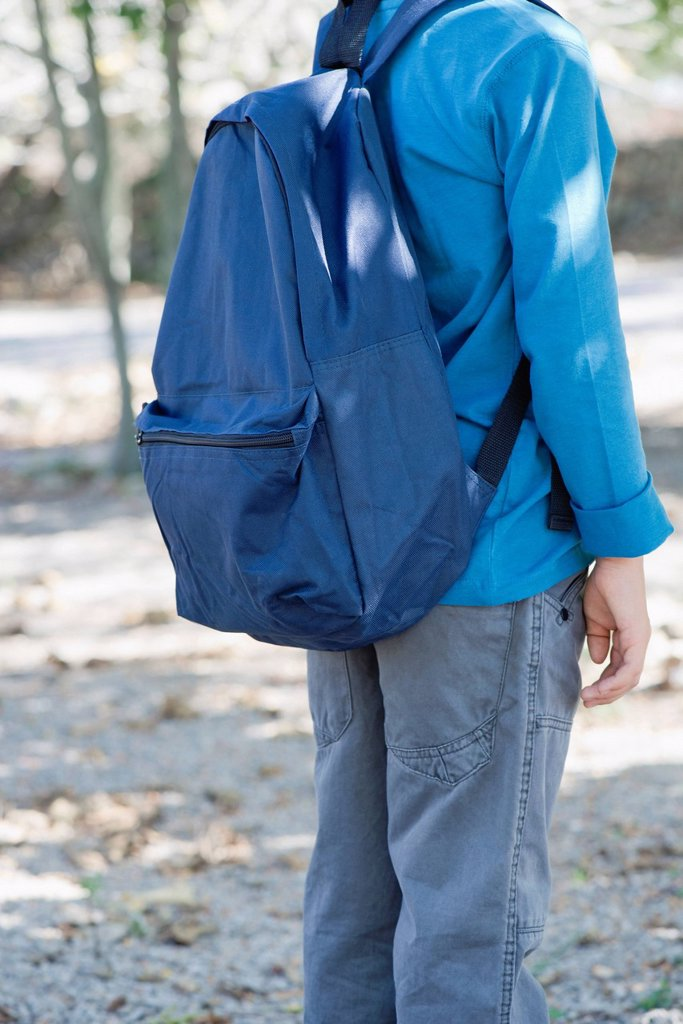 Stock Photo: 1569R-9072198 Boy carrying backpack, mid section