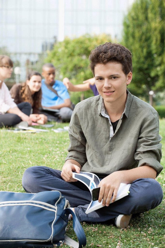 Young man sitting on grass, people in background, portrait : Stock Photo